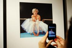 A woman takes picture of a framed Marilyn Monroe photo at gallery in Warsaw August 6, 2012. REUTERS/Kacper Pempel/Files
