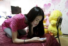 Online hostess Xianggong checks her mobile phone as she sits on her bed after a live broadcast in Beijing, February 10, 2015. REUTERS/Jason Lee