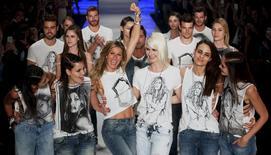 La modelo Gisele Bundchen levanta su brazo en medio de sus colegas tras participar en un desfile en Sao Paulo. Bundchen, la modelo mejor pagada del mundo, desfiló por última vez, en la semana de la moda de Sao Paulo, después de una carrera de 20 años en el mundo de la moda. REUTERS/Paulo Whitaker