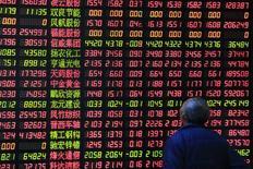 Инвестор в брокерской конторе в Шанхае. 17 марта 2015 года. Китай разрешит портфельным управляющим предоставлять акции взаймы для последующих продаж без покрытия и расширит перечень бумаг, доступных для игры на понижение, в попытке увеличить предложение акций на рынке. REUTERS/Aly Song