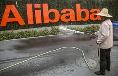 La firma china Alibaba Group ha sido multada con 800.000 yuanes (129.000 dólares) por la autoridad de precios de la provincia de Zhejiang por violaciones realizadas por terceros vendedores durante las promociones de las plataformas de comercio electrónico del gigante del comercio electrónico En la imagen, un hombre riega el cartel de Alibaba en Hangzhou el 21 de septiembre de 2013.  REUTERS/Chance Chan