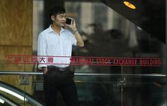 A man talks on the phone inside the Shanghai Stock Exchange building at the Pudong financial district in Shanghai November 17, 2014.  REUTERS/Carlos Barria