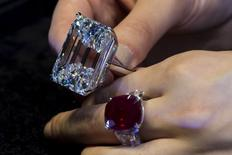 A model displays both a 100.20 carats (top) and a 25.59 carats, that is known as 'The Sunrise Ruby', diamond rings at a pre-auction viewing at Sotheby's in Hong Kong April 3,2015. REUTERS/Tyrone Siu