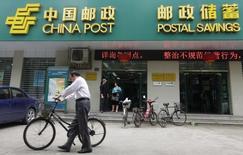 Мужчина у отделения Postal Savings Bank of China в Ухане. 4 мая 2012 года. UBS, сингапурский Temasek Holdings и французский BNP Paribas - среди дюжины предварительных претендентов на покупку до 10 процентов государственного Почтово-сберегательного банка Китая (PSBC) как минимум за $3 миллиарда, сказали Рейтер источники, знакомые с ситуацией. REUTERS/Stringer