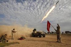 """Бойцы-шииты выпускают ракету во время столкновений с силами Исламского государства на окраинах аль-Аляма 8 марта 2015 года. Россия вооружает Ирак и Сирию, чтобы помочь им бороться с боевиками """"Исламского государства"""", сказал в среду глава МИДа Сергей Лавров, назвав исламских экстремистов главной угрозой безопасности. REUTERS/Thaier Al-Sudani"""