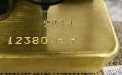 Una máquina marca un lingote de oro de 99,99 por ciento de pureza en la planta Krastsvetmet en Krasnoyarsk, Rusia, feb 27 2014. El oro tocó su menor nivel en más de una semana el miércoles y tuvo la mayor pérdida de una sesión en más de seis semanas, tras un reporte que mostró sólidas ventas de casas en marzo en Estados Unidos, lo que alentó las expectativas de que la Reserva Federal eleve las tasas de interés en junio.  REUTERS/Ilya Naymushin