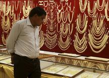 Мужчина в ювелирном магазине в городе Коччи на юге Индии. 21 апреля 2015 года. Цены на золото держатся чуть выше трехнедельного минимума после наиболее сильного за месяц спада за счет укрепления доллара. REUTERS/Sivaram V
