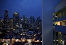 A man returns to his flat at the end of the work day at a Housing Development Board (HDB) public housing estate overlooking the financial district skyline in Singapore in this August 20, 2014 file photo.  REUTERS/Edgar Su