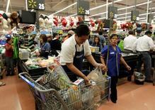 Un trabajador empaqueta unas compras al interior de un supermercado Wal-Mart en Ciudad de México, nov 21 2011. Las ventas al menudeo de México subieron un 0.5 por ciento en febrero contra enero, por segundo mes consecutivo, apuntando a una lenta recuperación del consumo, según cifras divulgadas el viernes por el instituto nacional de estadísticas, INEGI.   REUTERS/Henry Romero