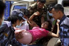 Militares e voluntários carregam uma mulher ferida ao hospital Dhading, após o terremoto de sábado, em Dhading Besi, no Nepal, nesta segunda-feira. 27/04/2015 REUTERS/Athit Perawongmetha