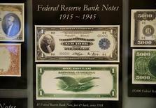 Старые долларовые купюры в Вашингтоне 14 ноября 2014 года. Курс доллара близок к двухмесячному минимуму накануне объявления итогов совещания ФРС. REUTERS/Gary Cameron
