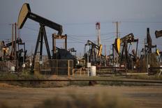 Станки-качалки на нефтяном месторождении в Калифорнии. 20 апреля 2015 года. Цены на нефть останутся относительно низкими еще как минимум год, показал опрос Рейтер. REUTERS/Lucy Nicholson