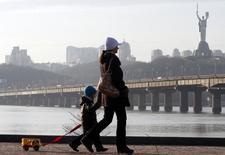 Женщина с ребенком идут по набережной Днепра в Киеве. 30 ноября 2012 года. Украина завершила первый квартал 2015 года с профицитом государственного бюджета на сумму 4,169 миллиарда гривен ($189 миллионов) по сравнению с дефицитом в размере 4,094 миллиарда за аналогичный период прошлого года, сообщило министерство финансов. REUTERS/Anatolii Stepanov