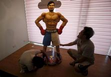 Baker Zach Yonson (R) and an assistant put finishing touches on a life-size 70-kg chocolate cake of local boxing icon Manny Pacquiao at a restaurant in Manila, Philippines May 2, 2015.  REUTERS/Erik De Castro