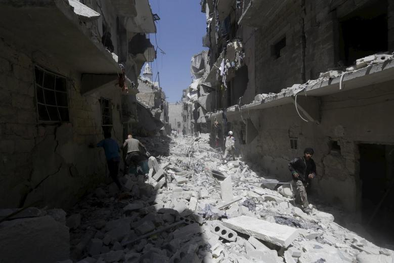 Residents walk amidst debris at a site damaged by what activists said was a barrel bomb dropped by forces loyal to Syria's president Bashar Al-Assad al-Sukkari neighborhood of Aleppo, May 1, 2015. REUTERS/Hosam Katan