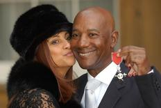 Errol Brown of British band Hot Chocolate holds his MBE (Member of the Order of the British Empire) with his wife Ginette after receiving the award for his services to pop music, from Britain's Queen Elizabeth II at Buckingham Palace, November 27, 2003. REUTERS/POOL/Fiona Hanson/Files