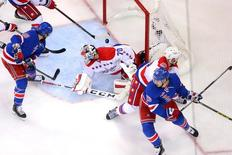 May 8, 2015; New York, NY, USA; Washington Capitals defenseman Matt Niskanen (2) clears the puck away after Washington Capitals goalie Braden Holtby (70) makes a save against New York Rangers center J.T. Miller (10) during the second period of game five of the second round of the 2015 Stanley Cup Playoffs at Madison Square Garden. Mandatory Credit: Brad Penner