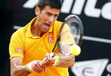 Novak Djokovic of Serbia returns the ball to Nicolas Almagro of Spain during their match at the Rome Open tennis tournament in Rome, Italy, May 12, 2015. REUTERS/Tony Gentile