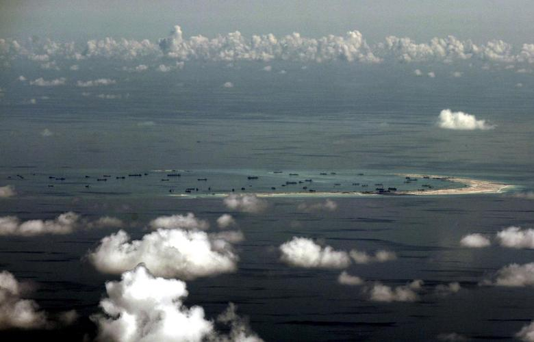 An aerial photo taken though a glass window of a Philippine military plane shows the alleged on-going land reclamation by China on mischief reef in the Spratly Islands in the South China Sea, west of Palawan, Philippines, May 11, 2015.  REUTERS/Ritchie B. Tongo