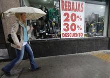 Una persona pasa frente a una tienda con descuentos en sus artículos en Buenos Aires, sep 5 2014. Los precios minoristas de Argentina habrían subido un 1,2 por ciento promedio en el cuarto mes del año, liderados por el rubro educación, según un sondeo de Reuters publicado el miércoles.        REUTERS/Enrique Marcarian