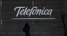 La consolidación de E-Plus y un efecto divisa favorable permitió al gigante español de las telecomunicaciones Telefónica crecer en ingresos y resultado bruto de explotación en el primer trimestre del año, mientras el beneficio se vio impulsado por un fuerte efecto fiscal en la venta de O2 en Reino Unido. En la imagen, un hombre habla por teléfono reflejado en una tienda de Telefónica  en el centro de Madrid, el 28 de abril de 2015. REUTERS/Sergio Pérez