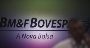 Un hombre habla por teléfono en frente del logo de la brasileña BM&FBovespa, en Sao Paulo, 7 de octubre de 2013. La Bolsa de Sao Paulo BM&FBovespa SA, la cuarta del mundo, planea seguir comprando participaciones de sus rivales en Latinoamérica hasta donde las actuales regulaciones imponen un límite, afirmó el viernes su presidente ejecutivo, Edemir Pinto. REUTERS/Nacho Doce