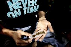 Un hombre enrolla un cigarro de cannabis durante una concentración en demanda de la legalización del cannabis, en la Plaza Síntagma, en Atenas, 9 de mayo de 2015. Los consumidores de cannabis que buscan a alguien para compartir un cigarro tienen una nueva aplicación que les permite hallar a fumadores de marihuana en todo el mundo.   REUTERS/Kostas Tsironis
