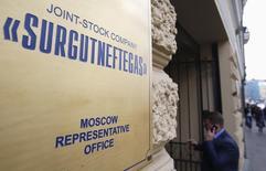 """Мужчина у входа в офис Сургутнефтегаза в Москве. 23 сентября 2014 года. Совет директоров Сургутнефтегаза рекомендовал общему собранию в 3,5 раза увеличить дивиденды по привилегированным акциям за 2014 год, выплатив 8,21 рубля на """"преф"""" после 2,36 рубля за 2013-й, сообщила компания в пятницу. REUTERS/Maxim Zmeyev"""