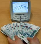 Работник банка в Санкт-Петербурге проверяет подлинность 1000-рублевых купюр 4 февраля 2010 года. REUTERS/Alexander Demianchuk