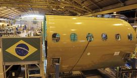 Un empleado trabaja en la línea de ensamblaje de jets, en la sede de Embraer, en Sao José dos Campos, cerca de Sao Paulo, 14 de mayo de 2013. El fabricante brasileño de aviones Embraer SA firmó un contrato para vender 30 aeronaves E195-E2 a la aerolínea local Azul Linhas Aéreas SA, el primer pedido firme en virtud a un acuerdo por el que la operadora aérea podría comprar hasta 50 unidades, dijo Embraer en un comunicado el jueves. REUTERS/Nacho Doce