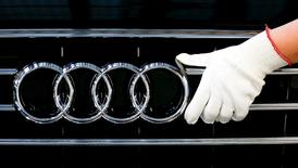 A worker fixes a car emblem as he assembles Audi A8 models at their plant in Neckarsulm near Heilbronn May 21, 2015. Audi will hold their annual shareholders meeting on May 22, 2015.   REUTERS/Michael Dalder