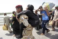 Membro das forças de segurança do Iraque retira idosa em ponte nos arredores de Bagdá. 24/05/2015 REUTERS/Stringer