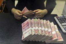 """Un empleado contando billetes de 100 yuan, en una sucursal del China Merchants Bank, en Hefei, provincia de Anhui, 20 de abril de 2015. La moneda china, el yuan, dejó de estar subvaluada luego de su reciente apreciación sustancial, pero el Gobierno debe acelerar las reformas para llegar a tener """"una tasa de cambio flotante"""", dijo el martes el Fondo Monetario Internacional. REUTERS/Stringer"""
