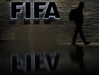 Мужчина у входа в штаб-квартиру ФИФА в Цюрихе. 20 октября 2010 года. Высокопоставленные функционеры ФИФА взяты под стражу в Швейцарии и ждут экстрадиции в США, которые выдвинули против них обвинения в коррупции, сообщили американские газеты о расследовании, длившемся годы. REUTERS/Christian Hartmann