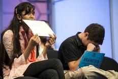 Eesha Sohail (L) of Bakersfield, California, bites her name placard while Marcus Behling of Scottsdale, Arizona, rubs his eyes during the semi-final round of the 88th annual Scripps National Spelling Bee at National Harbor, Maryland May 28, 2015. REUTERS/Joshua Roberts