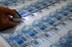 Funcionário inspeciona notas de 100 reais na Casa da Moeda, no Rio de Janeiro. 23/08/2012 REUTERS/Sergio Moraes