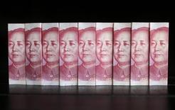 Купюры валюты юань в Пекине 11 июля 2013 года. Нефтяное крыло Газпрома, компания Газпромнефть, в 2014 году начав расчеты с Китаем за поставки углеводородов в юанях, распространила эту практику на 2015-й, сообщила компания. REUTERS/Jason Lee