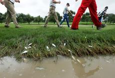 May 29, 2015; Irving, TX, USA; Jordan Spieth and caddies walk down the 11th fairway past a flooded area of the rough with dead minnows during the second round of the AT&T Byron Nelson Championship at TPC Four Seasons Resort - Las Colinas. Mandatory Credit: Erich Schlegel-USA TODAY Sports