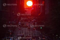 "People crowd onto 42nd Street as they take photos of the ""Manhattanhenge"" phenomenon in the Manhattan borough of New York July 11, 2014.  REUTERS/Carlo Allegri"