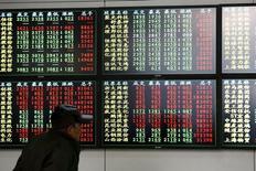 Un inversor mira la información mostrada en una pantalla electrónica en una agencia de la bolsa, en Shanghái, 8 de diciembre de 2014. El euro extendía su avance el jueves gracias a un alza en los rendimientos de la deuda de la zona euro, mientras que las volátiles acciones chinas retrocedían. REUTERS/Aly Song