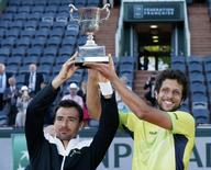 Ivan Dodig of Croatia (L) and Marcelo Melo of Brazil pose with their trophy after defeating Bob Bryan and Mike Bryan of the U.S. in their men's doubles final match at the French Open tennis tournament at the Roland Garros stadium in Paris, France, June 6, 2015.