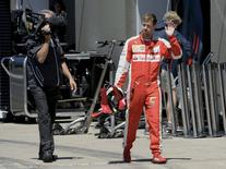 Ferrari Formula One driver Sebastian Vettel of Germany waves while walking back to his team's garage during the qualifying session of the Canadian F1 Grand Prix at the Circuit Gilles Villeneuve in Montreal June 6, 2015. REUTERS/Paul Chiasson/Pool