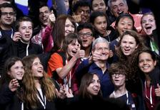 Apple CEO Tim Cook poses with scholarship winners following his keynote address at the Worldwide Developers Conference in San Francisco, California June 8, 2015.  REUTERS/Robert Galbraith
