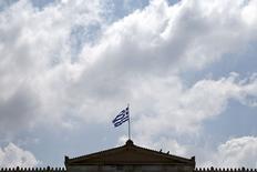 Una bandera de Grecia flameando sobre un edificio en Atenas, jun 9 2015. Funcionarios griegos que han estado negociando un acuerdo de deuda con los acreedores de Atenas regresaron a su país el jueves, dijo una fuente griega a Reuters, luego que el FMI anunció que su equipo también había dejado la capital belga debido a las diferencias entre las partes. REUTERS/Alkis Konstantinidis