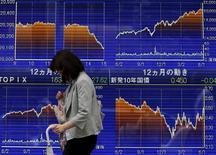 Una mujer camina frente a un tablero electrónico que muestra las variaciones del índice Nikkei, afuera de una agencia de la bolsa, en Tokyo, 9 de junio de 2015. El índice Nikkei de la bolsa de Tokio cerró estable el lunes luego de que un estancamiento en las negociaciones entre Grecia y sus acreedores y la cautela antes de una reunión del comité de política monetaria de la Reserva Federal de Estados Unidos desalentaron las compras. REUTERS/Issei Kato