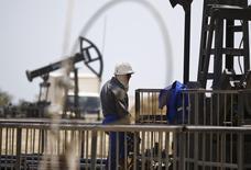 A worker rests next to an oil pump on a sunny day in Baku, Azerbaijan, June 16 , 2015. REUTERS/Kai Pfaffenbach