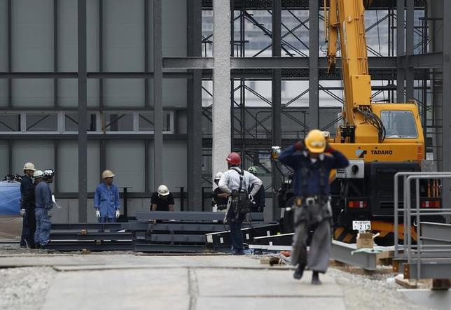 People work near heavy machinery at a construction site in Tokyo August 14, 2014. REUTERS/Yuya Shino/Files