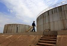 Un empleado de la empresa petrolera canadiense Pacific Rubiales, camina cerca del tanque de depósito de petróleo, en Meta, al este de Colombia, 11 de febrero de 2015. La producción industrial de Colombia se contrajo un 3,6 por ciento interanual en abril, informó el martes el Departamento Nacional de Estadísticas (DANE). REUTERS/Jose Miguel Gomez