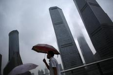 A man walks in the rain along the financial district of Pudong in downtown Shanghai August 18, 2014.  REUTERS/Carlos Barria