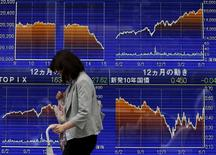 Una mujer camina frente a un tablero electrónico que muestra las variaciones del índice Nikkei, afuera de una agencia de la bolsa, en Tokyo, 9 de junio de 2015. El índice Nikkei de la bolsa de Tokio cayó el jueves a un mínimo en un mes, pasando por debajo de la marca de los 20.000 puntos por primera vez desde mediados de mayo, por el fortalecimiento del yen después que la Reserva Federal de Estados Unidos señaló que subirá las tasas de interés a un ritmo más lento que lo previsto. REUTERS/Issei Kato